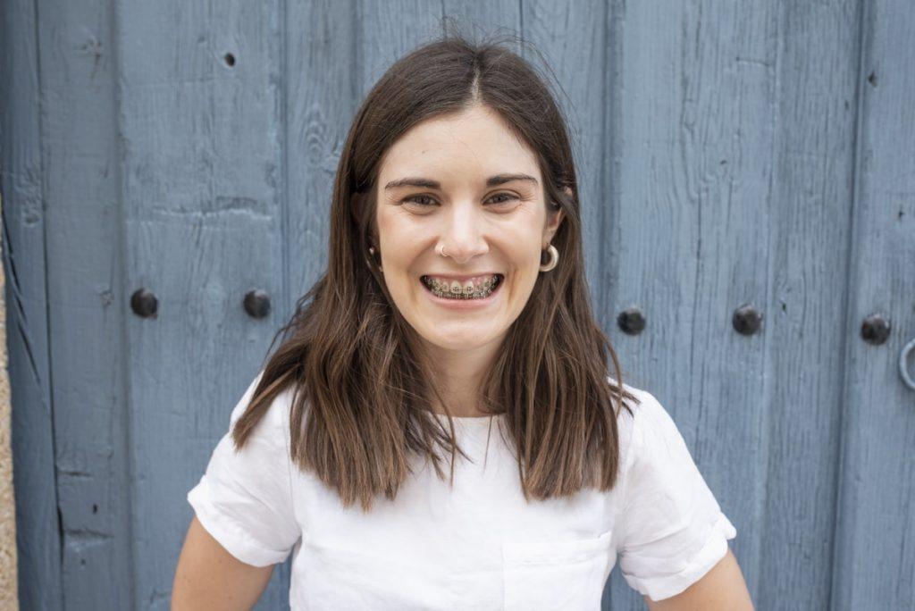 Laura sonriendo delante de puerta azul pueblo