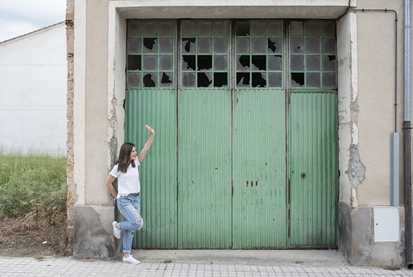Laura apoyada en portada verde saludando Cantalejo Segovia